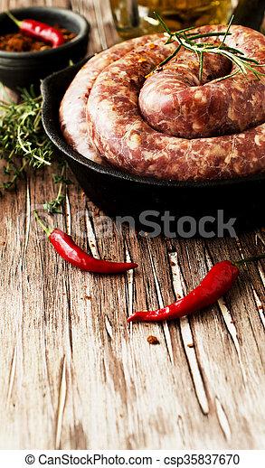 raw beef sausages on a cast-iron pan,  selective focus - csp35837670