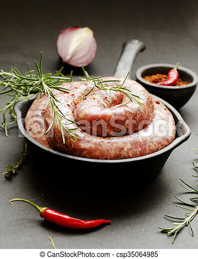 raw beef sausages on a cast-iron pan,  selective focus - csp35064985