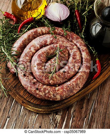 raw beef sausages on a cast-iron pan,  selective focus - csp35067989