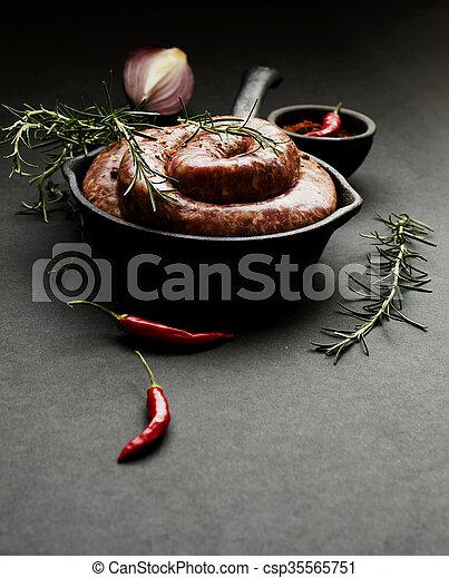 raw beef sausages on a cast-iron pan,  selective focus - csp35565751