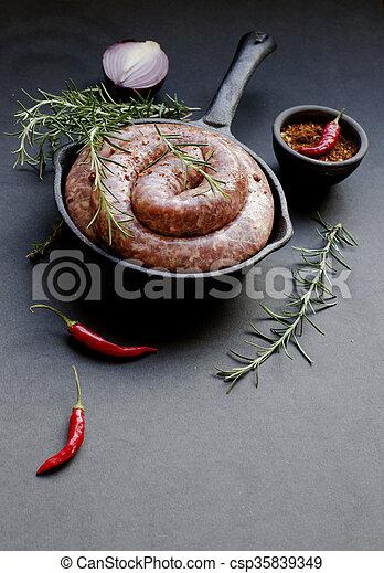 raw beef sausages on a cast-iron pan,  selective focus - csp35839349