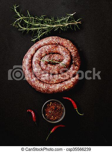 raw beef sausages on a cast-iron pan,  selective focus - csp35566239