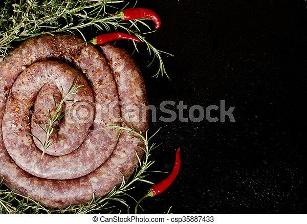 raw beef sausages on a cast-iron pan,  selective focus - csp35887433