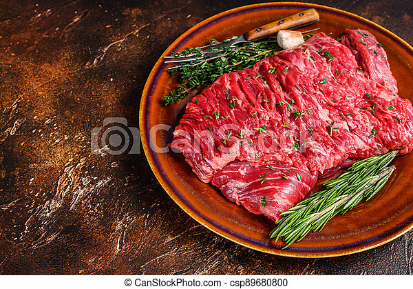 Raw beef skirt meat steak on a rustic plate with herbs. Dark background. Top view. Copy space - csp89680800