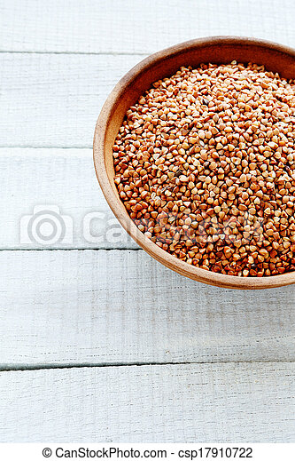 raw buckwheat in bowl on wooden background - csp17910722