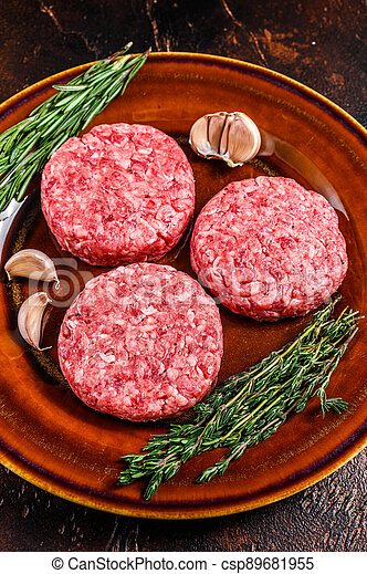 Raw burger meat cutlets with mince beef and herbs on a plate. Dark background. Top view - csp89681955