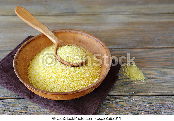 Raw couscous in a clay bowl on wooden boards - csp22592611
