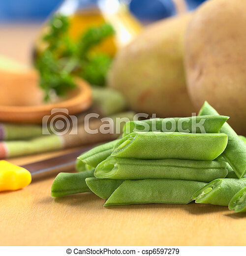 Raw cut green bush beans on wooden board with a kitchen knife, potatoes, parsley and oil in the back (Selective Focus, Focus on the three beans lying on each other) - csp6597279