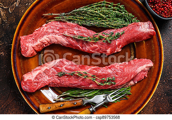 Raw flank beef meat steak on a plate. Dark background. Top view - csp89753568