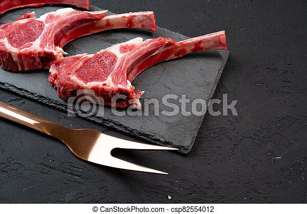 Raw fresh lamb ribs on dark background - csp82554012