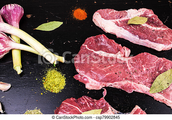 Raw, fresh meat and spices on a black wooden background. Marbled beef with spices - csp79902845
