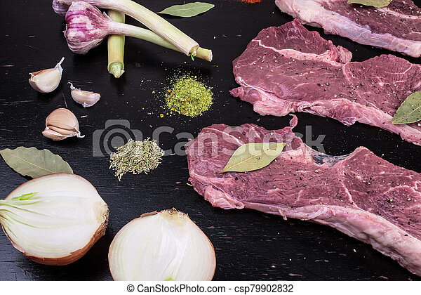 Raw, fresh meat and spices on a black wooden background. Marbled beef with spices - csp79902832