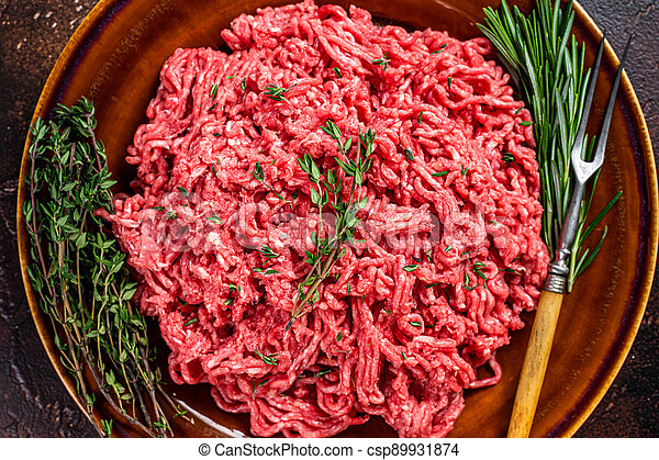 Raw ground beef or veal meat on a rustic plate with herbs. Dark background. Top view - csp89931874