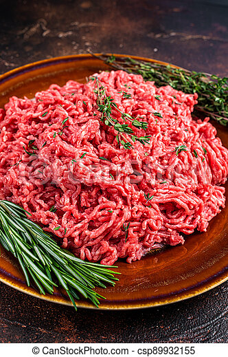 Raw ground beef or veal meat on a rustic plate with herbs. Dark background. Top view - csp89932155