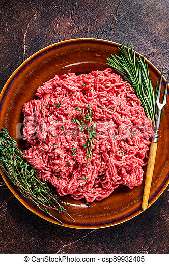 Raw ground beef or veal meat on a rustic plate with herbs. Dark background. Top view - csp89932405