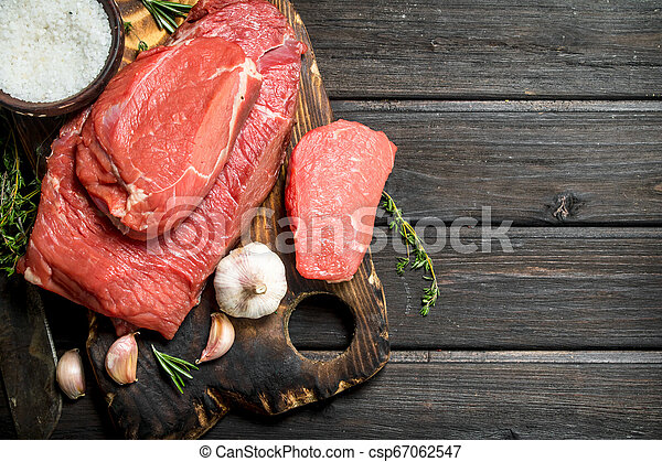 Raw meat. Pieces of fresh beef with garlic and spices. - csp67062547