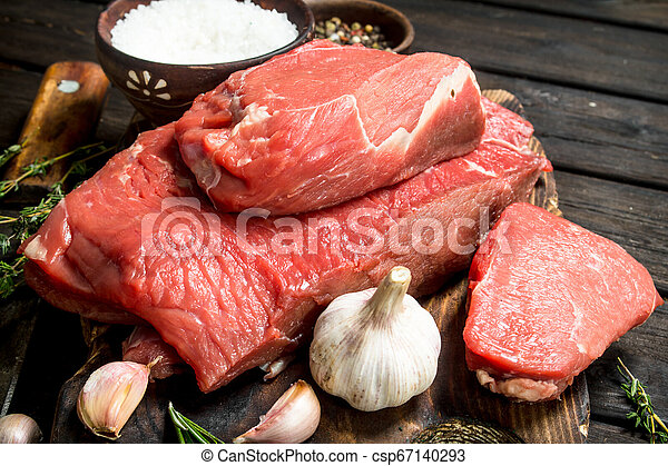 Raw meat. Pieces of fresh beef with garlic and spices. - csp67140293