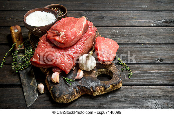 Raw meat. Pieces of fresh beef with garlic and spices. - csp67148099