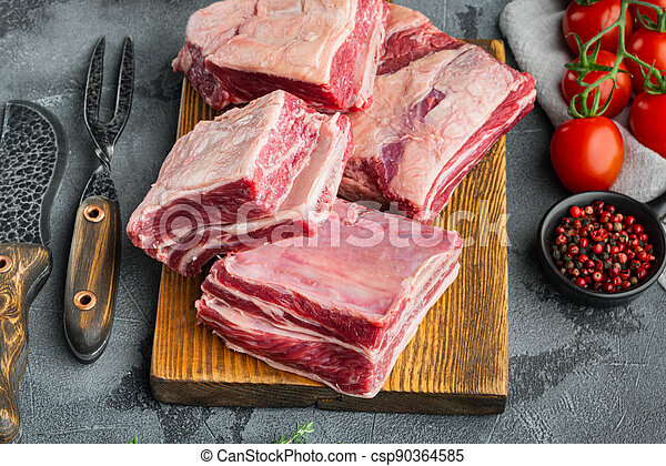 Raw meat ribs, with ingredients , on gray stone background - csp90364585