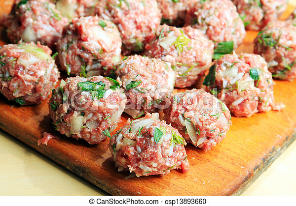 Raw meatballs on the chopping board - csp13893660