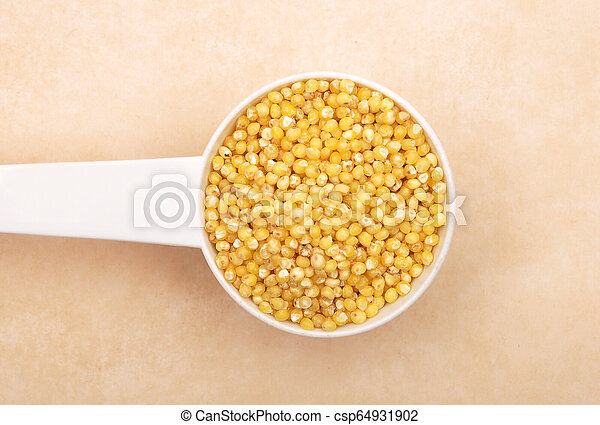 Raw millet in measuring spoon on brown background - csp64931902