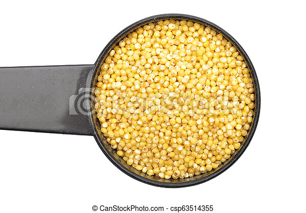 Raw millet in measuring spoon on white background - csp63514355