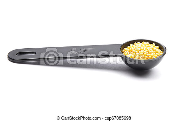 Raw millet in measuring spoon on white background - csp67085698