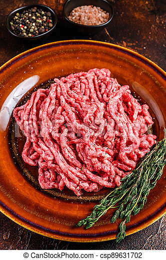 Raw mince angus wagyu beef, ground meat with herbs on a plate. Dark background. Top view - csp89631702