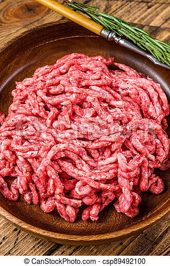 Raw mince lamb, ground mutton meat with herbs on a plate. Wooden background. Top view - csp89492100