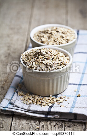 Raw oat flakes in ceramic bowls on linen napkin, golden wheat ears on rustic wooden background. - csp69370112