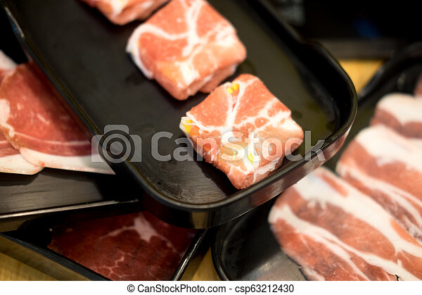 Raw pork for hot pot in black container - csp63212430