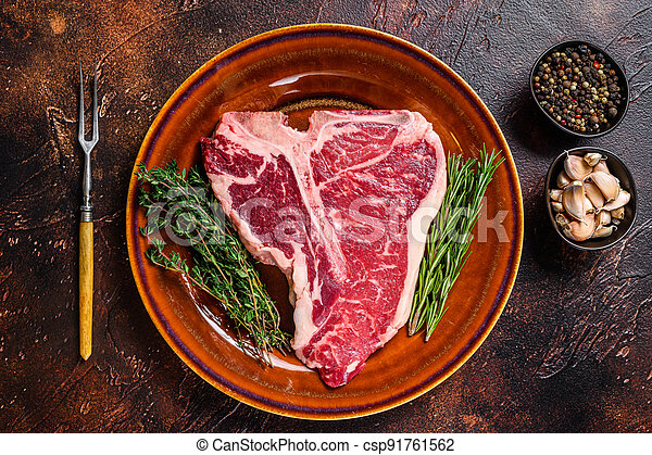 Raw porterhouse beef meat Steak with herbs on a plate. Dark background. Top view - csp91761562