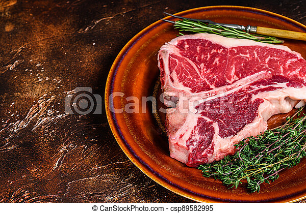 Raw porterhouse beef meat Steak with herbs on a plate. Dark background. Top view. Copy space - csp89582995