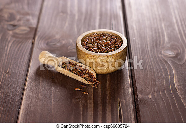 Raw red rice on brown wood - csp66605724