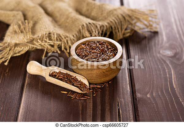 Raw red rice on brown wood - csp66605727