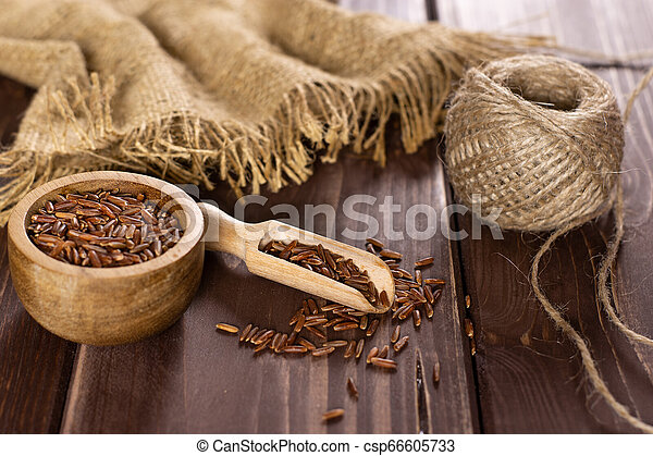 Raw red rice on brown wood - csp66605733