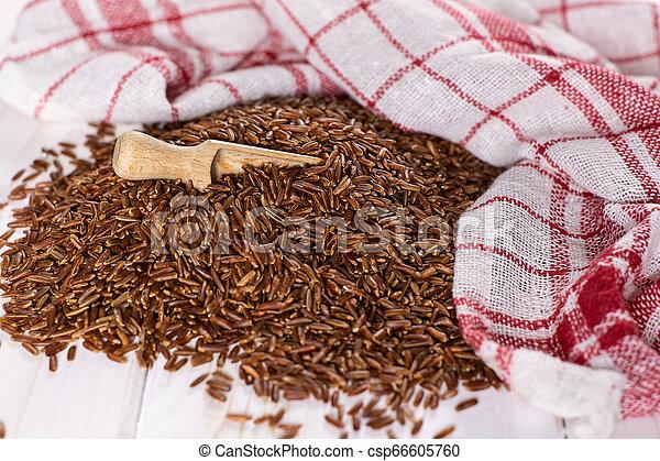 Raw red rice on grey wood - csp66605760
