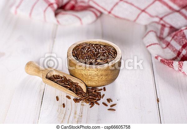 Raw red rice on grey wood - csp66605758