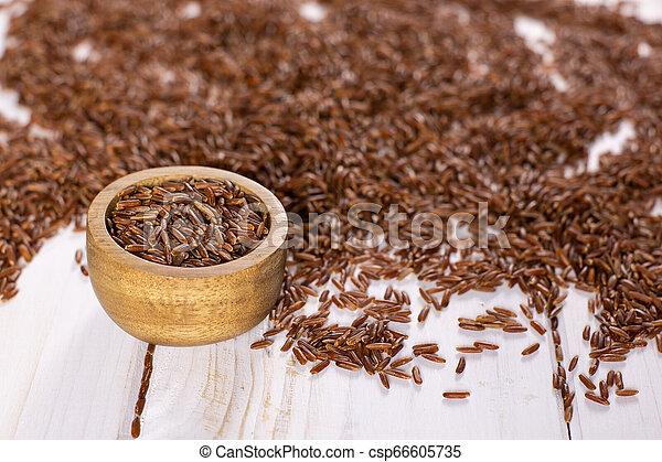 Raw red rice on grey wood - csp66605735