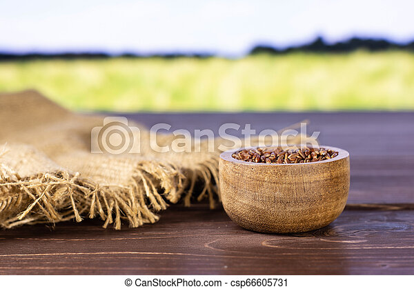 Raw red rice with field behind - csp66605731