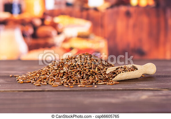 Raw red rice with rustic kitchen - csp66605765