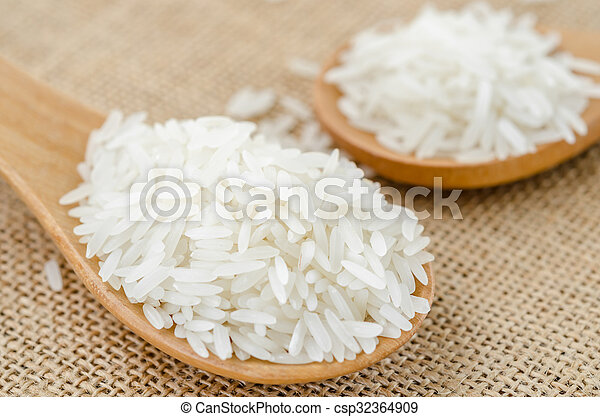 Raw rice in wooden spoon. - csp32364909