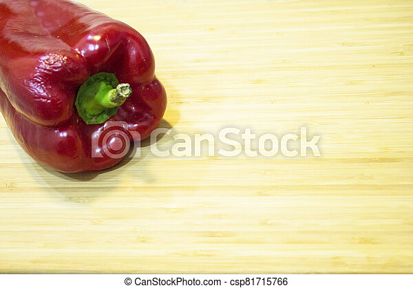 Raw ripe red pepper on cutting board - csp81715766