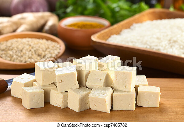 Raw tofu cut in dices on wooden board with rice and other raw ingredients in the back (Selective Focus, Focus on the front of the tofu) - csp7405782