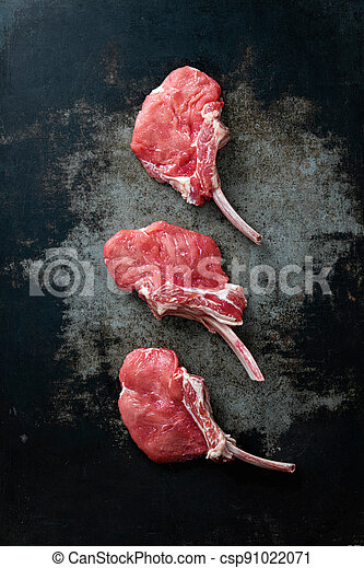 Raw veal Frenched Racks meat with ingredients on rustic dark background - csp91022071