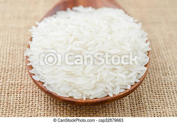 Raw white rice in wooden spoon. - csp32879663