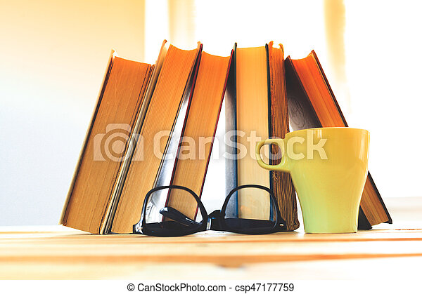 reading glasses with books on the table - csp47177759
