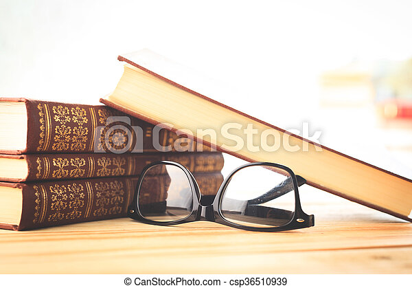 reading glasses with books on the table - csp36510939