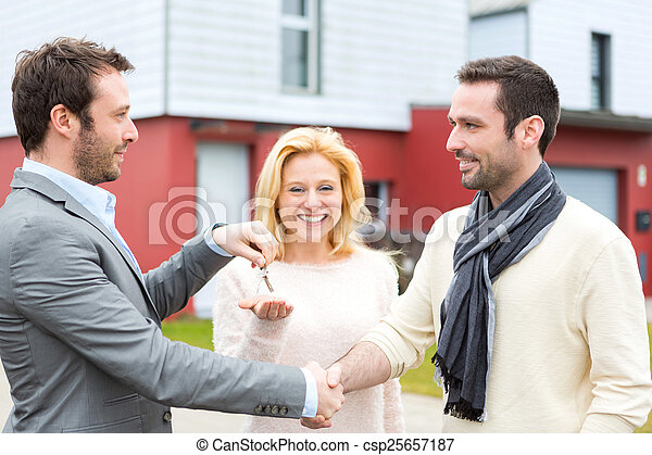 Real estate agent delivers keys to young atractive couple - csp25657187