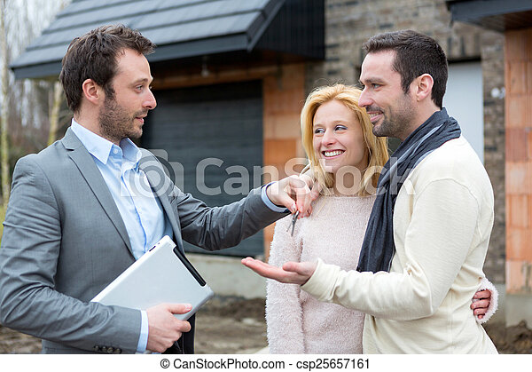 Real estate agent delivers keys to young atractive couple - csp25657161
